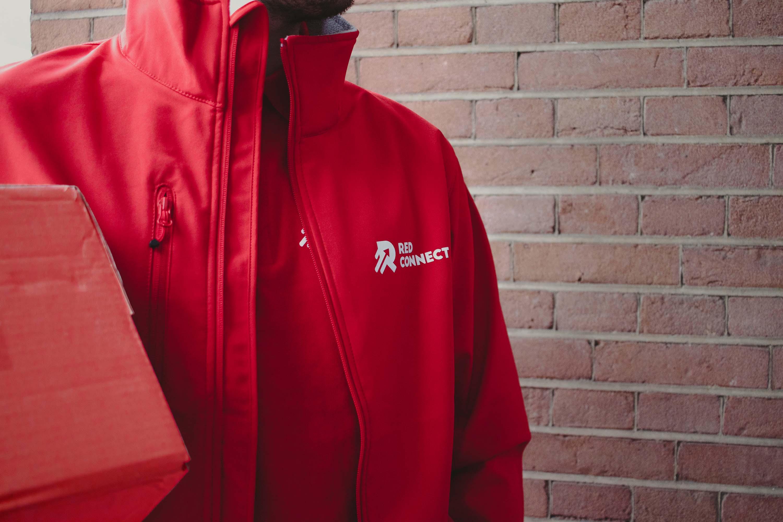 Close-up van een Red Connect monteur in rode jas.